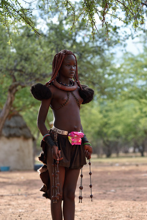 KAMANJAB, NAMIBIA - FEB 1, 2016: Young unidentified Himba woman with typical hairstyle shown in himba village