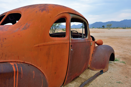 corroding: SOLITAIRE, NAMIBIA - JAN 30, 2016: Damaged abandoned old Hudson car at the service station at Solitaire in the Namib Desert, Namibia. Popular touristic destination Editorial