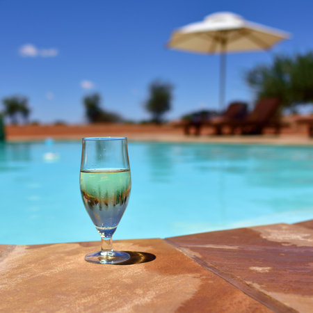 misted: Misted glass of white wine with ice on the border of the swimming pool in the middle of Kalahari Desert. Concept exotic luxury vacation. Small depth of field