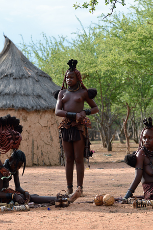 nude women: KAMANJAB, NAMIBIA - FEB 1, 2016: Unidentified Himba women with the typical necklace and hairstyle shown in himba tribe village