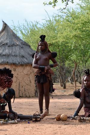 Kamanjab, Namibia - Feb 1, 2016: las mujeres Himba no identificados con el collar y el peinado típico se muestran en la aldea de la tribu himba