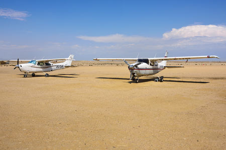 swakopmund: SWAKOPMUND, NAMIBIA - JAN 31, 2016: Two Cessna airplanes on the small airport near Swakopmund. Popular tourist attraction in Namibia - flight safaris above Namib desert Editorial