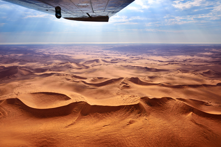 Beautiful landscape of the Namib Desert under the wing of the aircraft at sunset. Flying on a plane over the desert is one of the most popular tourist attractions in Namibia Imagens
