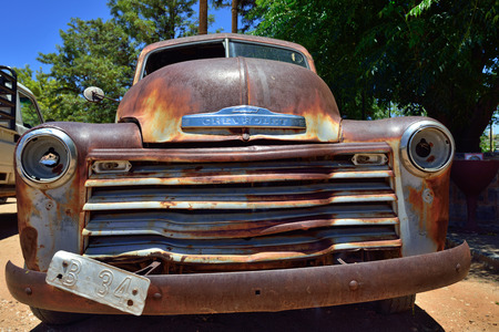 corrosion: SOLITAIRE, NAMIBIA - JAN 30, 2016: Damaged abandoned old Chevrolet car at the service station at Solitaire in the Namib Desert, Namibia. Popular touristic destination