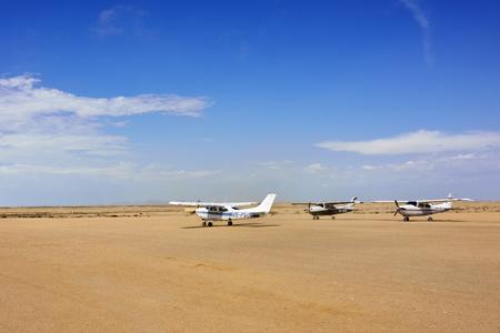 swakopmund: SWAKOPMUND, NAMIBIA - JAN 31, 2016: Cessna airplane takes off on the small airport near Swakopmund. Popular tourist attraction in Namibia - flight safaris above Namib desert