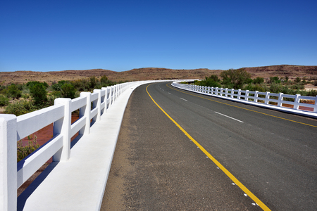 namib: A newly tarred road with white fence in Namib desert, Namibia, Africa