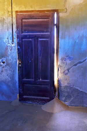 seeps: The sand seeps through a crack in the door. The abandoned ghost diamond town of Kolmanskop in Namibia, which is slowly being swallowed by the desert Stock Photo