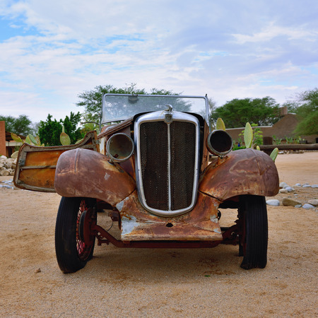old service station: SOLITAIRE, NAMIBIA - JAN 30, 2016: Damaged abandoned old Morris Eight  car at the service station at Solitaire in the Namib Desert, Namibia. Popular touristic destination Editorial