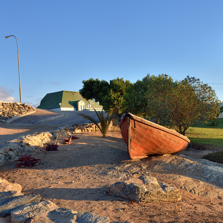 luderitz: Luderitz street scene, old boat at sunset. Luderitz is a harbour town in southwest Namibia, lying on one of the least hospitable coasts in Africa Stock Photo