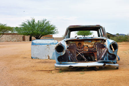 corroding: SOLITAIRE, NAMIBIA - JAN 30, 2016: Damaged abandoned old car at the service station at Solitaire in the Namib Desert, Namibia. Popular touristic destination