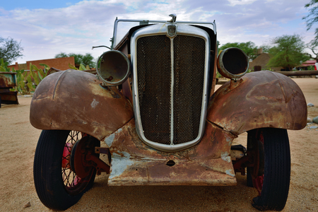 solitaire: SOLITAIRE, NAMIBIA - JAN 30, 2016: Damaged abandoned old Morris Eight  car at the service station at Solitaire in the Namib Desert, Namibia. Popular touristic destination Editorial