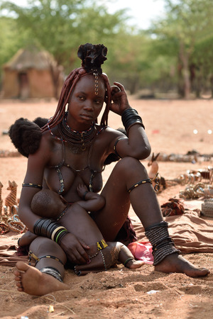 nude nature: KAMANJAB, NAMIBIA - FEB 1, 2016: Young unidentified Himba woman with typical hairstyle and her baby shown in himba village Editorial