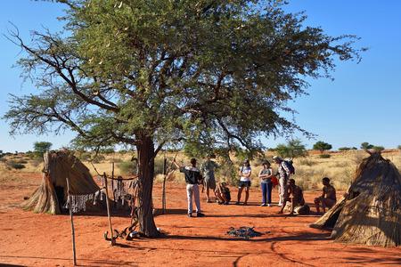 KALAHARI, NAMIBIA - JAN 24, 2016: Tourists visit bushmen tribe village. The San people, also known as Bushmen are members of various indigenous hunter-gatherer peoples of Southern Africa