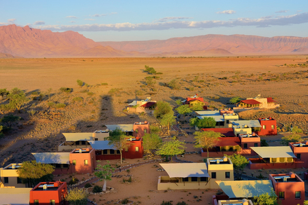 above 30: SOSSUSVLEI, NAMIBIA - JAN 30, 2016: Accommodation units in the Sossusvlei Lodge. View from above at sunset. The most popular place in Namib-Naukluft park.