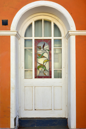 20th century: Architecture detail. Door with stained glass of the historical building built in the early 20th century in Luderitz Stock Photo