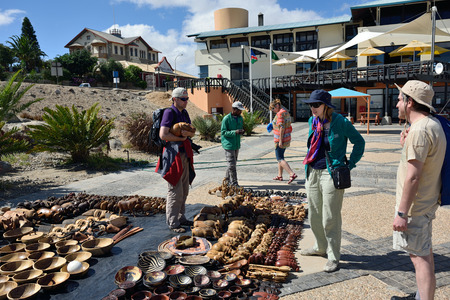 frippery: LUDERITZ, NAMIBIA - JAN 27, 2016: Tourists shown on the craft market in Luderitz. Local hand made toys and other african goods very popular between tourists Editorial