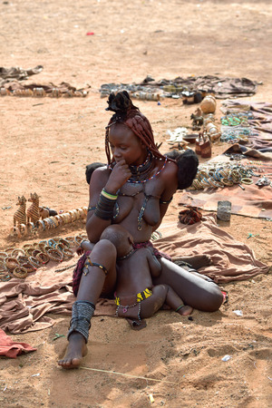 northern african: KAMANJAB, NAMIBIA - FEB 1, 2016: Young unidentified Himba woman with typical hairstyle and her baby shown in himba village Editorial