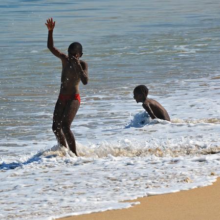 swakopmund: SWAKOPMUND, NAMIBIA - JAN 31, 2016: Children have a fun in water on the beach in Swakopmund. Swakopmund was founded in 1892, by Captain Curt von Francois as the main harbour of German South West Africa