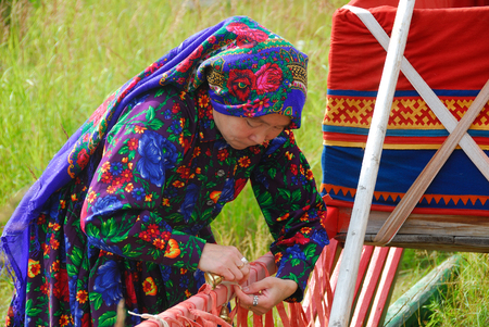 YAMAL, RUSSIA - AUG 27, 2009: Small peoples of the Russian North. Yamal-Nenets Autonomous District. Khanty herder woman decorated a sleigh in herders camp Redakční