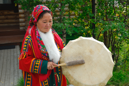YAMAL, RUSSIA - AUG 27, 2009: Small peoples of the Russian North. Yamal-Nenets Autonomous District. Khanty herder woman in national dress shown with tambourine