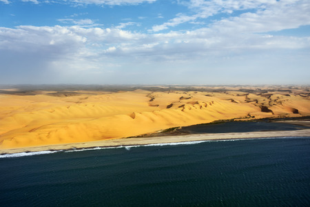 Aerial view on the coast in Namibia where dunes of the Namib desert meet with Atlantic ocean, Africa Stock Photo