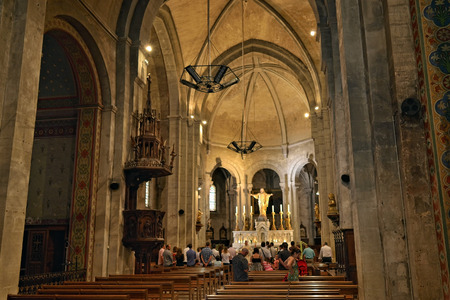inhabitants: MAZAN, FRANCE � JUL 19, 2014: Church service at the church in Mazan. Mazan is a town of 4500 inhabitants, with the old town protected by its circled wall of buildings dating from the 14th century Editorial