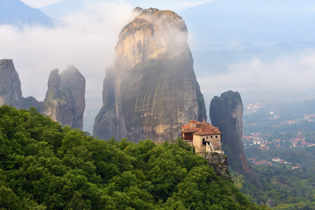 Meteora monasteries. Beautiful view on the Holy Monastery of Roussanov placed on the edge of high rock covered of the morning clouds and mist at sunrise, Kastraki, Greece Editorial