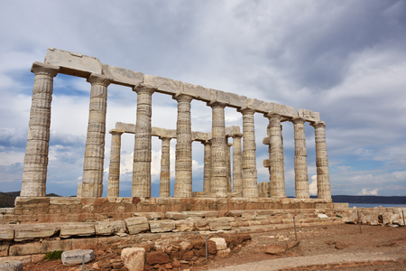 poseidon: Greece. Cape Sounion - Ruins of an ancient Greek temple of Poseidon before sunset under dramatic cloudy sky