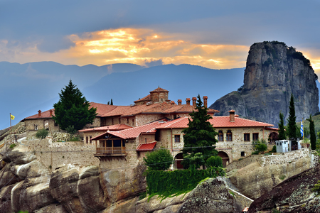 Meteora monasteries. Beautiful view on Monastery of the Holy Trinity placed on the edge of high rock against the beautiful sunset, Kastraki, Greece