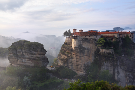 kalambaka: Meteora monasteries. Beautiful view on the Holy Monastery of Great Meteofo placed on the edge of high rock covered of the morning clouds and mist at sunrise, Kastraki, Greece