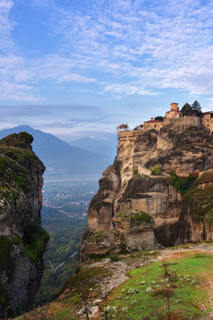 Meteora monasteries. Beautiful view on the Holy Monastery of Varlaam placed on the edge of high rock covered of the morning clouds and mist at sunrise, Kastraki, Greece Stock Photo