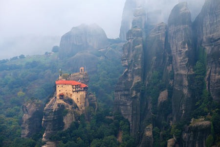 Meteora monasteries. View on the Holy Monastery of St Nikolaos Anapafsas placed on the edge of high rock and covered morning mist, Kastraki, Greece