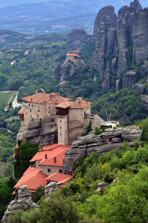 inaccessible: View from above on the Meteora landscape and Holy Monastery Roussanov at sunrise, Monastery of St Nikolaos Anapafsas on background, Meteora, Greece
