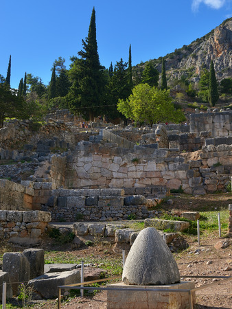 Famous ancient marble Navel Stone also known as Omphalos in Ancient Greek archaeological site of Delphi shown at warm evening light, Central Greece Stock Photo