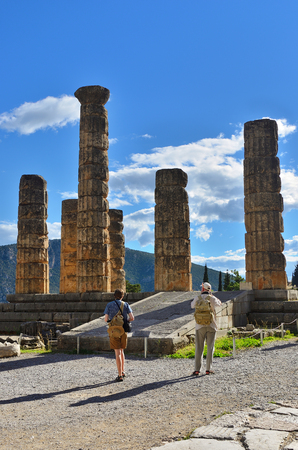 delphi: Delfi, Greece - Sept 20, 2016: Tourist visit the Apollo Temple in Delphi, an archaeological site in Greece, at the Mount Parnassus. Delphi is famous by the oracle at the sanctuary dedicated to Apollo Editorial