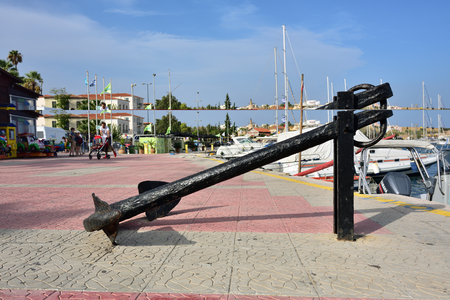 brigt: Lavrion, Greece - Sept 18, 2016: Big vintage anchor on the seafront in small town Lavrion in Attica. Greece very popular place of destination for spending time during vacation