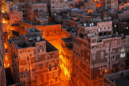 inhabited: Yemen. Night view of the old city of Sanaa from above. Inhabited for more than 2.500 years at an altitude of 2.200 m, the Old City of Sanaa is a UNESCO World Heritage City now destroyed by the civil war Stock Photo