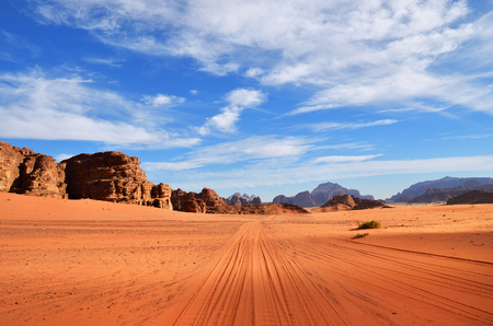 Dirt road in the Wadi Rum (Moon Valley) desert landscape at sunset time, Jordan