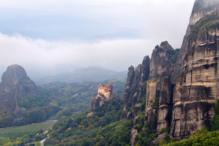 Meteora monasteries. View on beautiful landscape and the Holy Monastery of St Nikolaos Anapafsas placed on the edge of high rock covered of the morning clouds and mist at sunrise, Kastraki, Greece