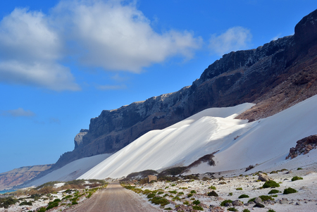 Empty dirt road between Indian ocean and big white sand dunes on the shore of Socotra island shown at twilight. Yemen Stock Photo