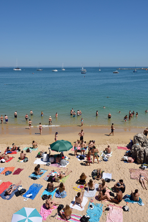 portugese: CASCAIS, PORTUGAL - JUNE 07, 2017: People sunbathing on the Praia da Rainha public beach. Cascais is famous and popular summer vacation spot for Portuguese and foreign tourists