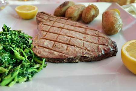 Grilled tuna steak with green boiled broccoli and batatas a murro, or smashed potatoes is a traditional Portuguese dishes