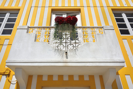 Balcony with flowers of the house in famous resort Costa Nova on the Atlantic coast in Beira Litoral, Portugal. Popular tourist destination to spend vacation time