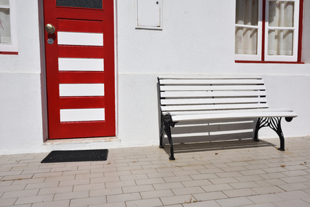 Detail of the house in famous resort Costa Nova on the Atlantic coast in Beira Litoral, Portugal.  Red door and white bench. Popular tourist destination to spend vacation time