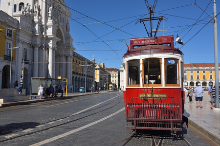 wood railways: LISBON, PORTUGAL – June 11, 2017: Vintage red tram shown on the square Praca de Comercio (Commerce square), Rua Augusta triumphal arch on background