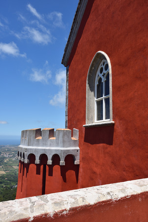 plastered wall: Detail of Pena National Palace in Sintra in Portugal. Red plastered wall with window and balcony Stock Photo