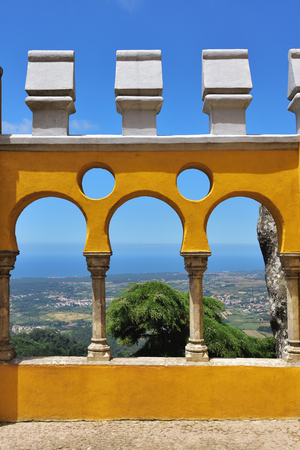 Detail of the Pena National Palace in Sintra in Portugal. Yellow plastered fence, Sintra area background on background