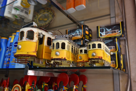 replica: Sintra, Portugal - June 07, 2017: Street shop with models vintage yellow trams as souvenirs. Very popular purchases by tourists in Portulal