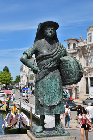 touristy: AVEIRO, PORTUGAL - JUNE 10, 2017: View on Peasant woman and main city canal. Aveiro, known as Venice of Portugal, also known for its production of salt
