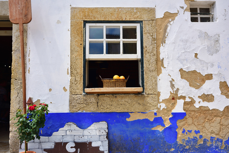 portugal agriculture: Basket with fresh bright oranges in the open window of the house. Obidos, Portugal Stock Photo
